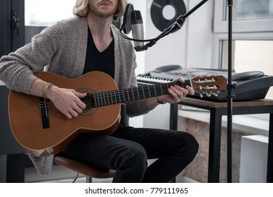 Confident male musician is playing string musical instrument in his studio. Focus on the acoustic guitar