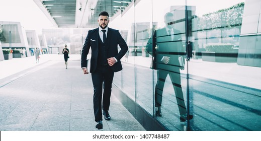 Confident male owner of company walking in city with modern netbook in hand, serious Caucasian businessman dressed in formal expensive suit going to corporate conference in financial district