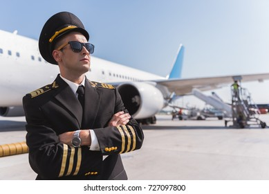 Confident male pilot standing outside