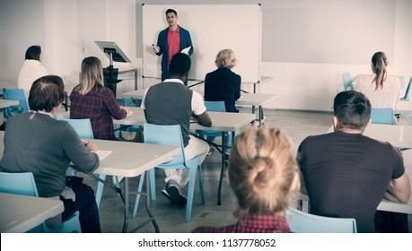 Confident male student answering at whiteboard in front group of students in auditorium