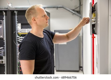 Confident Male Technician Opening Fire Panel In Datacenter