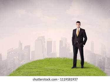 A confident male well looking office manager standing in small green grass in front of city landscape with tall buildings concept.