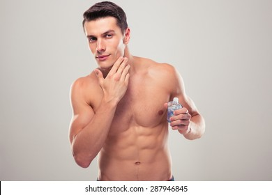 Confident man applying facial lotion over gray background
