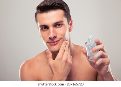 Confident man applying lotion after shave on face over gray background. Looking at camera