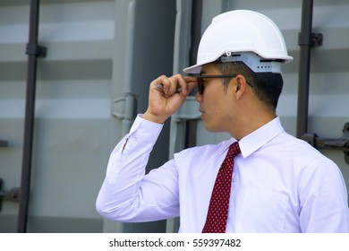 Confident man Architect or engineer  wears white shirt with burgundy neck tie is working with blue print. Idea for Safety or man working at site or field trip.