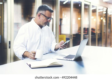 Confident man boss in casual white shirt checking e-mail via cellphone before meeting with staff.Male professional employer is typing text message on mobile phone while drink coffee in office interior