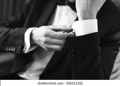 Confident man buttons cufflinks. Cufflinks closeup. Men's suit, tuxedo.