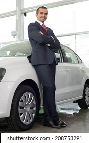 Confident man in formalwear leaning at the car and looking at camera while standing at car dealership