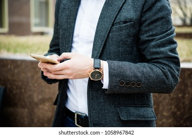 Confident man in gray jacket using smartphone, elegant business