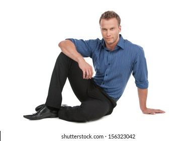 Confident man. Handsome young man in shirt sitting on the floor and looking at camera while standing isolated on white