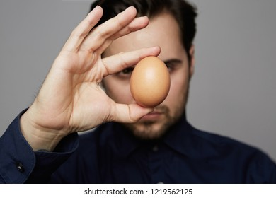 Confident man holding chicken fresh organic egg front of FACE ON GRAY BACKGROUND. Close up