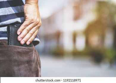 Confident man keeping wallet in the back pocket of his back pocket pants. savings money.