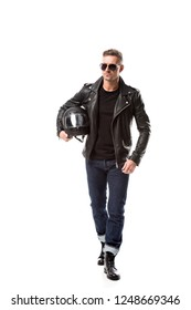 confident man in leather jacket and sunglasses holding motorcycle helmet isolated on white