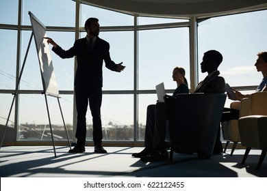 Confident man pointing at blank whiteboard at seminar