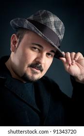 Confident man portrait with hat on dark background.