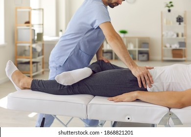 Confident man professional doctor osteopath fixing man patinets legs in position to fix joints during visit at rehabilitation theapy in manual therapy clinic. Chiropractor during work concept