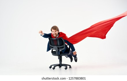 Confident man in a red cloak riding on a chair in a bright room