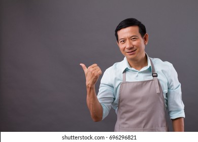 confident man shopkeeper pointing thumb up to space, concept of small business owner, shop manager, entrepreneur suggesting something