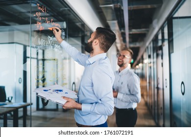 Confident man spending time for training business person writing information on modern board during cooperation with partner discussing ideas for startup project, accounting briefing in office