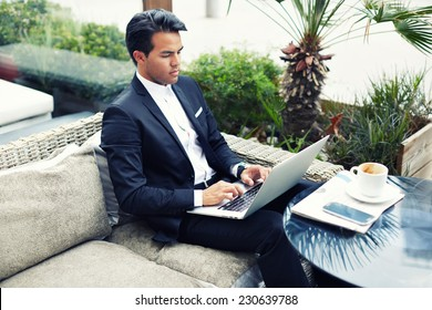Confident man in suit typing on laptop computer keyboard, businessman seated in cafe working with computer, businesspeople using modern devises, rich businessman working with laptop computer in cafe