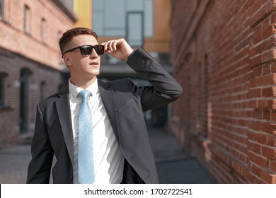 confident man in sunglasses and a formal suit poses against the background of a classic brick building. Concept of a real estate manager or lawyer career