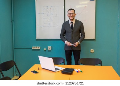 Confident man teacher standing near whiteboard in university classroom and smiling