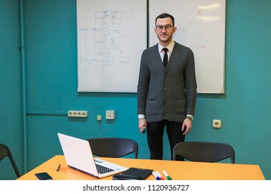Confident man teacher standing near whiteboard in university classroom
