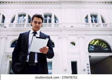 Confident man using digital tablet computer while standing in big light hall of railway station, successful businessman on way to work reading news on his touch pad, executive receiving news on email