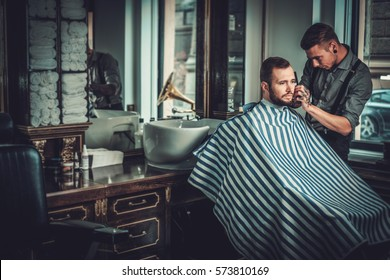 Confident man visiting hairstylist in barber shop
