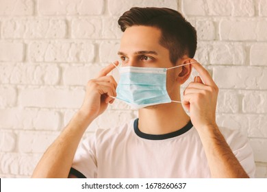 Confident man wearing medical mask on face for protection against coronavirus contagious disease. Young professional doctor putting on protective face mask as COVID-19, nCov-19 preventive measure