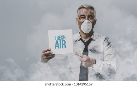 Confident man wearing a pollution mask and holding a fresh air sign