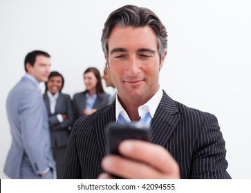 Confident manager sending a text with a mobile phone with his team in the background