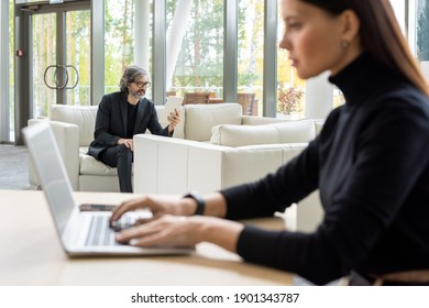 Confident mature broker in formalwear and eyeglasses sitting on soft white leather couch by window and looking through online financial data