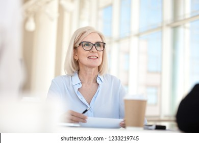 Confident mature business woman leader coach speaking at meeting negotiations, old middle aged female manager executive mentor talking participating in discussion at office conference briefing