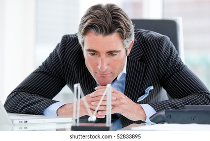 Confident mature businessman looking at kinetic balls sitting at his desk