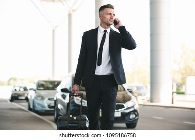 Confident mature businessman talking on mobile phone while walking outside the airport with a suitcase