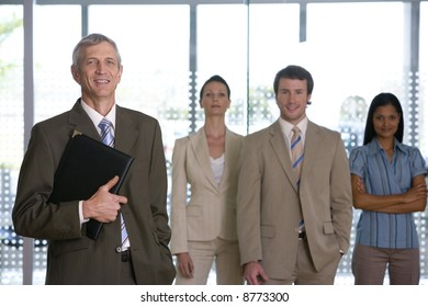 Confident mature businessman with team behind him