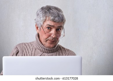 A confident mature businessman wearing glasses working with a laptop while being at home looking into camera with serious expression. People, lifestyle and technology concept.