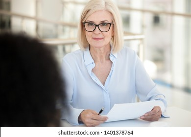 Confident mature businesswoman hold paper document, listen to colleague talk at company meeting, employees discuss project result, report, marketing plan, interview with intern in office close up