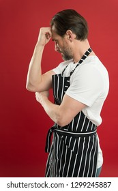 Confident mature handsome man in apron red background. He might be baker gardener chef or cleaner. Good in everything. Professional occupation. Apron for dirty work. Man in apron. Lot of work.