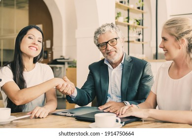 Confident mature investor shaking hands with young entrepreneurs. Man and women meeting over cup of coffee at co-working. Medium shot. Partnership and investment concept