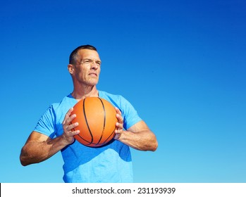 Confident mature man holding basketball against clear blue sky