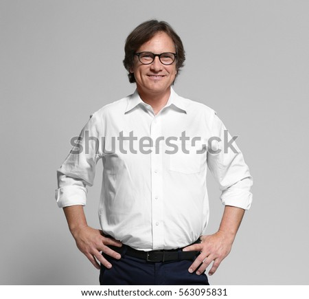Confident mature man on grey background