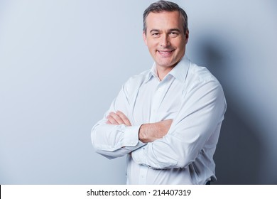 Confident mature man. Portrait of confident mature man in shirt looking at camera and smiling while keeping arms crossed and standing against grey background