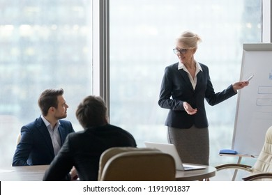 Confident mature mentor give flipchart presentation to office employees, middle-aged businesswoman explain project, drawing on whiteboard at company meeting, coach training millennial workers