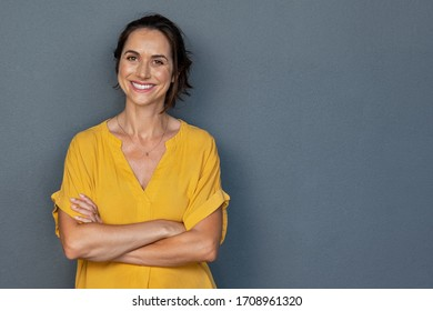 Confident mature woman with crossed arms in casual clothing with copy space. Successful smiling woman with big grin looking at camera. Beautiful positive businesswoman standing against grey background