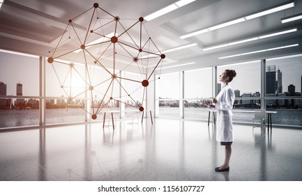 Confident medical industry employee standing inside white hospital building and examining black network structure. Modern technologies for medical industry