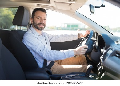 Confident mid adult owner sitting in driving seat of his car and smiling at camera