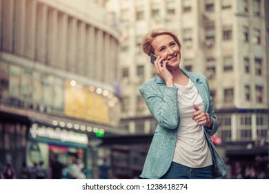 Confident mid-age woman talking on a cell phone in the street