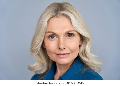 Confident middle aged blonde business woman looking at camera isolated on grey background. Successful proud older 50s lady professional coach, mentor, leader close up front face headshot portrait.